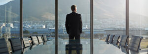 Man in suit looking out office window